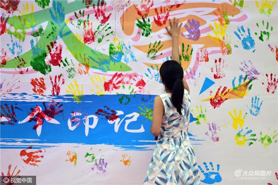 """学生会特别设置的迎新环节之一,让刚刚踏入校门的新生用手""""触摸""""大学图片"""