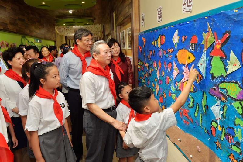 """一楼走廊展示了""""我的中国梦""""""""共筑碧水蓝天""""等主题活动的绘画,手工"""